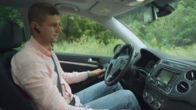 Conductor masculino positivo que usa el ordenador del viaje en coche metrajes