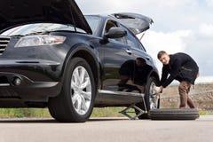 Conductor masculino que cambia su neumático en el borde de la carretera Imagen de archivo libre de regalías