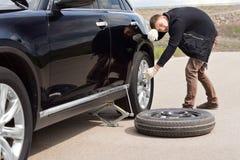 Conductor masculino que lucha para cambiar su neumático del coche Fotografía de archivo libre de regalías