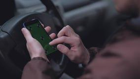 Conductor masculino que usa smartphone con la pantalla verde en el coche almacen de video