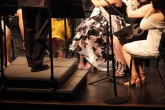 Conductor and musicians orchestra feet and legs. Formally dressed Feet and legs of a music orchestra preforming a concert on stage stock photography
