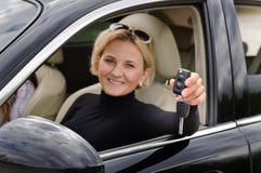 Conductor orgulloso de la mujer que soporta sus llaves del coche Fotografía de archivo libre de regalías