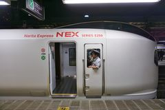 Conductor peering through the window of a high speed Narita Express train Royalty Free Stock Photography