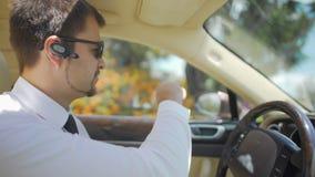Conductor profesional que conduce el automóvil costoso, comunicando con el pasajero almacen de metraje de vídeo