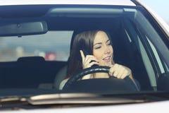Conductor que conduce un coche distraído en el teléfono Imagen de archivo libre de regalías