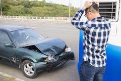 Conductor que mira el coche después de accidente de tráfico Foto de archivo