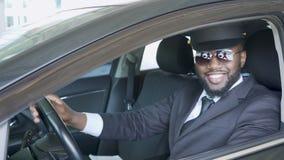Conductor que se sienta en el coche, ventana lateral que va abajo, sonrisa afroamericana, servicio metrajes