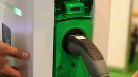 Conductor que tapa el vehículo eléctrico en zócalo, usando servicios de la estación de carga metrajes