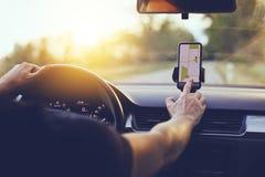 Conductor que usa la navegación GPS en teléfono móvil mientras que conduce el coche fotos de archivo libres de regalías
