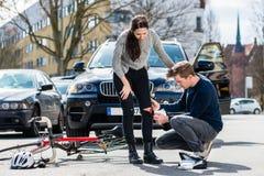 Conductor que usa un vendaje estéril para ayudar a un ciclista herido imagen de archivo libre de regalías