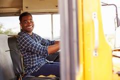 Conductor sonriente del autobús escolar que se sienta en autobús foto de archivo