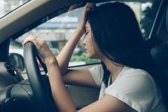 Conductor subrayado de la mujer que se sienta en el coche que tiene parada del dolor de cabeza después fotografía de archivo libre de regalías