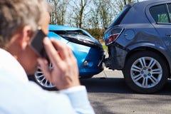 Conductor subrayado Sitting At Roadside después del accidente de tráfico Imagenes de archivo