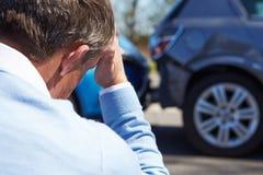 Conductor subrayado Sitting At Roadside después del accidente de tráfico Foto de archivo