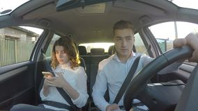 Conductor y novia en el coche que no presta la atención al camino ambas usando los teléfonos elegantes almacen de video