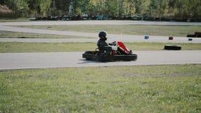 Conductores de Kart que mueven encendido una pista del kart del ir metrajes