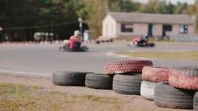 Conductores de Kart que mueven encendido una pista del kart del ir Neumáticos coloreados cerca de la pista almacen de video