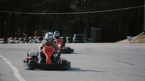 Conductores de Kart que mueven encendido una pista del kart del ir que pasa por la cámara metrajes