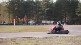Conductores de Kart que mueven encendido una pista del kart del ir que pasa por la cámara almacen de metraje de vídeo
