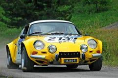 Conductores no identificados en un coche de competición alpino de Renault del vintage amarillo Fotografía de archivo libre de regalías