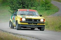 Conductores no identificados en un coche de competición amarillo del cupé de Opel Kadett C del vintage Imágenes de archivo libres de regalías