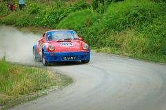 Conductores no identificados en un coche de competición rojo y azul de Porsche 911 S del vintage Foto de archivo