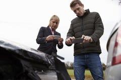 Conductores que toman la foto del accidente de tráfico en los teléfonos móviles foto de archivo