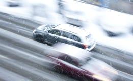 Conduire des voitures sur la rue neigeuse de ville Photos stock