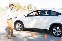 Conduire la voiture de stationnement d'Assisting Woman In de professeur photographie stock libre de droits