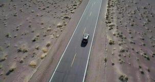 Conduire la voiture foncée de SUV sur la route dans Death Valley aux Etats-Unis banque de vidéos