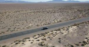 Conduire la voiture gris-foncé de SUV sur la route dans Death Valley aux Etats-Unis banque de vidéos