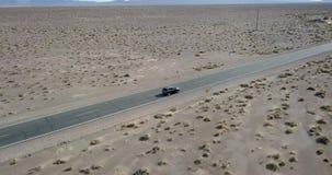 Conduire la voiture gris-foncé de SUV sur la route dans Death Valley aux Etats-Unis clips vidéos