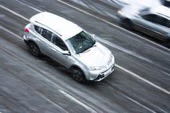 Conduire la voiture sur la rue neigeuse de ville Photo stock