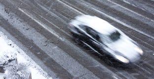 Conduire la voiture sur la rue neigeuse de ville dans la tache floue de mouvement Photos libres de droits