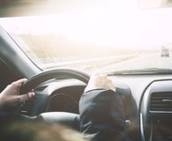 Conduire la voiture sur une route À l'intérieur de la vue du conducteur de femme Mains photos stock