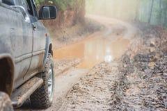 Conduire une voiture 4x4 sur une route boueuse pendant la saison des pluies, Off-r photos libres de droits