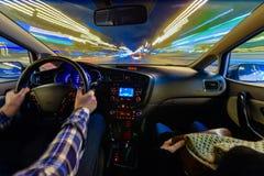 Conduisant dans le paysage de nuit, mains sur le volant, temps de pluie de nuit photos stock