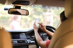 Conduisant et à l'aide du téléphone image stock