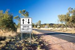 Conduisez sur le panneau routier d'avertissement gauche Photographie stock libre de droits