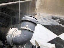 Conduit d'égout piqué dans un mur de briques et un tuyau de propylène photographie stock libre de droits