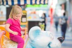 Conduite adorable de chéri sur le carrousel dans le mail Image libre de droits