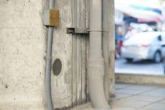 Conduite d'eau sur le mur et ligne éclectique sur la rue avec la vue de tache floue photographie stock