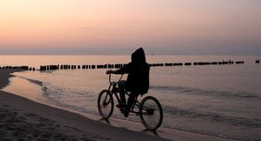 Conduite d'un vélo pendant le lever de soleil Photographie stock
