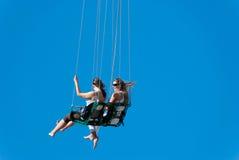Conduite de filles sur le carrousel à chaînes Images stock