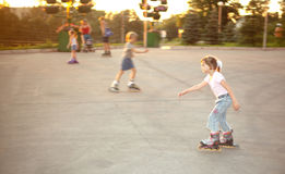 Conduite de gosses sur des patins de rouleau sur le patin Image libre de droits