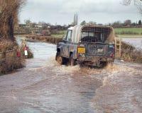 Conduite de véhicule par des eaux d'inondation sur la route Images stock
