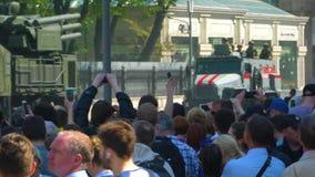 Conduite de véhicules militaire par les rues de la ville, et les personnes la filmant à son téléphone de caméra banque de vidéos