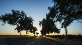 Conduite sur l'autoroute au coucher du soleil avec la tache floue de mouvement photographie stock libre de droits