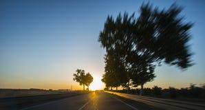 Conduite sur l'autoroute au coucher du soleil avec la tache floue de mouvement image stock