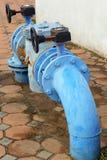 Conduites d'eau industrielles en métal rouillé bleu avec une valve photos libres de droits